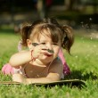Little girl laying in grass — Stock Photo