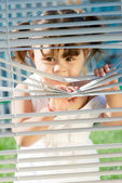 Little girl looking through the blinds — Stock Photo