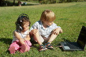 Boy and a girl with laptop in the park — Stok fotoğraf