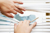 Hands apart on the window blinds — Stock Photo