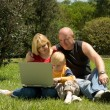 Mother father and son in the park studying laptop — Stock Photo