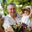 Little girl with grandfathers in the park — Stock Photo