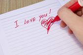 Persoon schrijft en tekent een hart met een rood potlood — Stockfoto