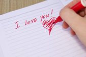 Person writes and draws a heart with a red pencil — Stock Photo