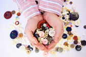 Buttons for sewing in the hands — Stock Photo