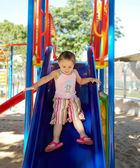 Girl riding on a swing on the playground — Stock Photo