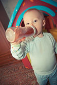 Young baby boy with bottle of juice — Stock Photo
