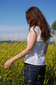 Girl standing in a yellow field — Stock Photo