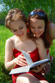 Two women reading the book — Stock Photo