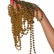 Gold beads in female hand — Stock Photo #1512464
