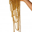Female hand hold gold beads. — Stock Photo #1838012