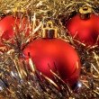 Three red spheres in a tinsel — Stok fotoğraf