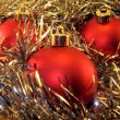 Three red spheres in a tinsel — Photo