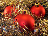 Three red spheres in a tinsel — Стоковое фото