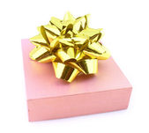 Gift in pink packing with gold bow — Stock Photo