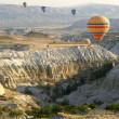 Hot air balloons above a gorgeous lands - Stock Photo