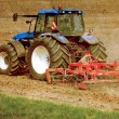 Grunge image of a tractor on farmland — Stock Photo