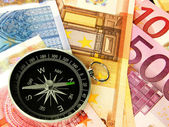 Currency and compass — Stock Photo