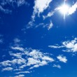 Sun and clouds on blue sky — Stock Photo