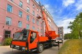 Red Heavy mobile crane truck with bilding — Stock Photo