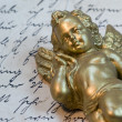 Little angel statue on old letter — Stock Photo