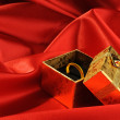 Gold boxes with a wedding ring on red si — Foto de Stock