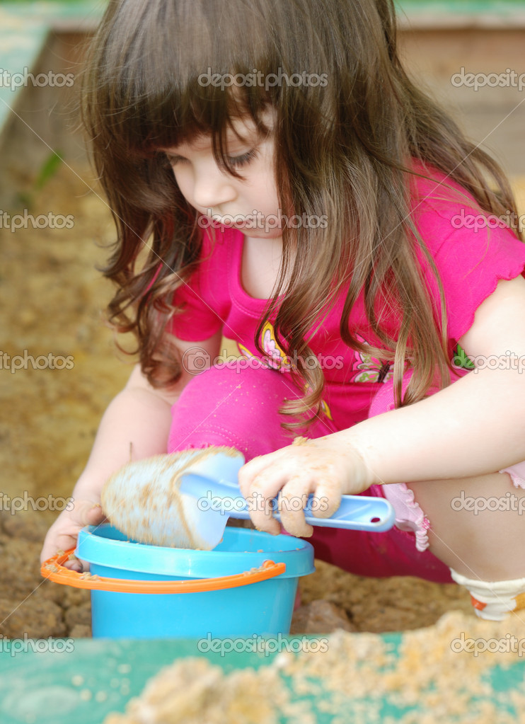 The girl playing to a sandbox. Caucasian the child, park of rest  Stock Photo #1524682