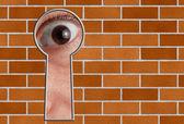 Olhar através de um buraco de fechadura na parede de pedra — Foto Stock