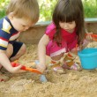 The boy and girl playing to a sandbox - Stok fotoğraf
