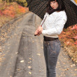 Girl in an autumn wood with a umbrella. — Stock Photo