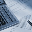 The calculator and the financial report — Stockfoto