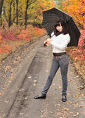 Girl in an autumn wood with a umbrella. — Stockfoto