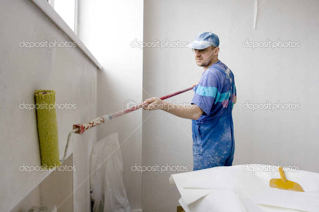 Master inflicts layer a glue for wallpaper on wall  Stock Photo #1533711