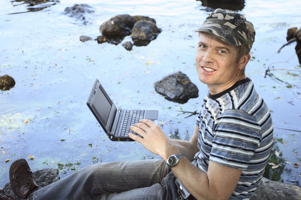 Man works at notebook sitting on stone — Stock Photo #1548343