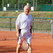 Royalty-Free Stock Photo: A aktive senior is playing tennis