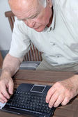 A senior with a Netbook — Stock Photo