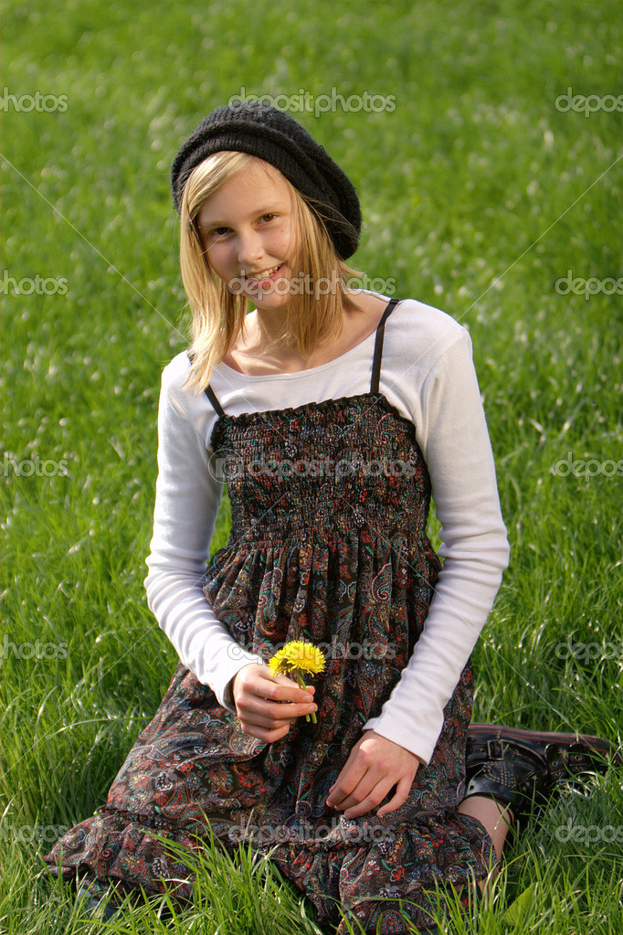 Blonde girl smiling and lies in the grass with a flower — Stock Photo #1536040