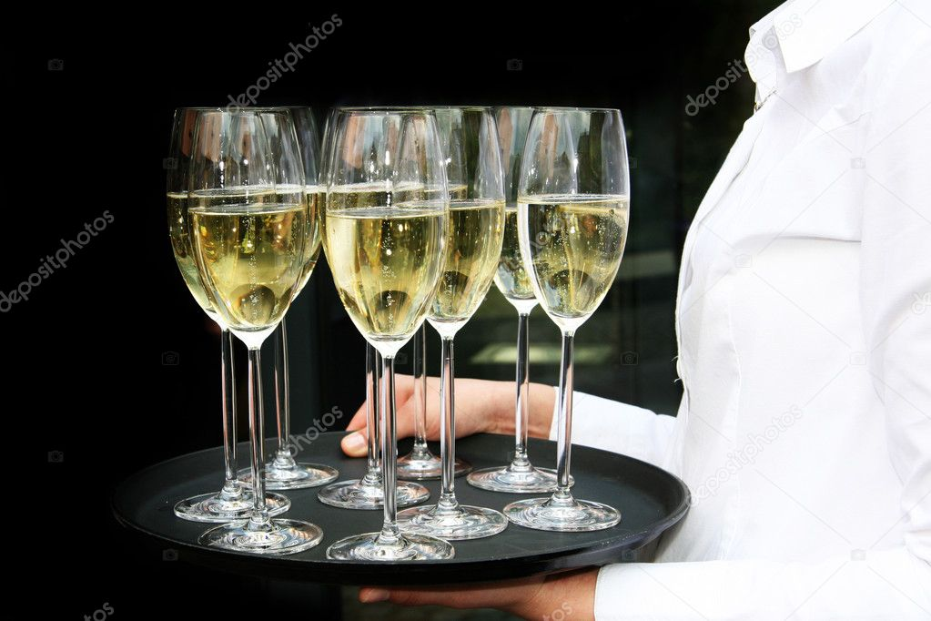 A waiter with champagne glasses on a tray. The background is black  Stock Photo #1838681