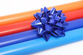 Colorful wrapping paper and a gift bow — Stock Photo