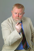 Businessman showing you with forefinger on grey background — Stock Photo