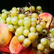 Grapes with peaches against black — Stock Photo