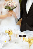 Bride with groom near table with glasses — Stock Photo
