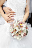Part of bride with bouquet of flowers — Stock Photo