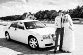 Bride and groom with a white car — ストック写真