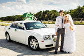 Bride and groom with a white car — Stock fotografie