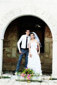 Newlyweds stands against a brick wall in the arch — Foto de Stock