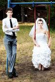 Bride sitting on swings and groom standing near — Foto de Stock