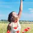Girl holding bottle on poppy field — Stock Photo