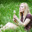 Girl blowing at dandelion in grass — Stock Photo