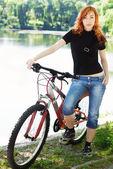 Garota em ganga com bicicleta — Foto Stock